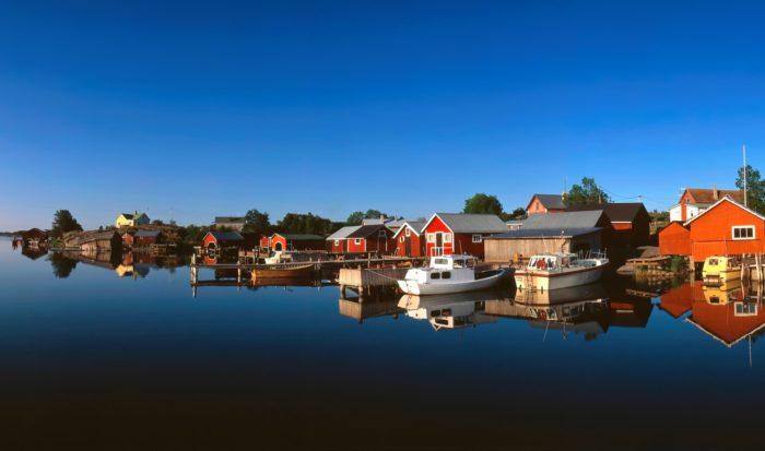 المياه الهادئة تعكس قرية على خط الشاطئ في كوكار، التي تقع جنوب شرق أولاند.