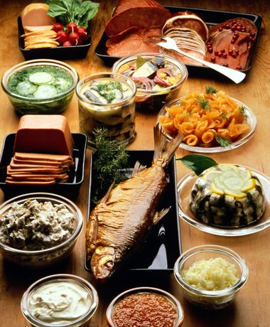 A table filled with different dishes, such as fish, pâté and pickles.