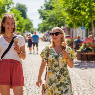 Two women walking in sunny streets of Mariehamn and eating icecream in summery clothes