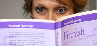 A person's eyes visible behind a Finnish grammar book.