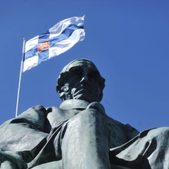 A flag is visible behind a statue of a sitting man.