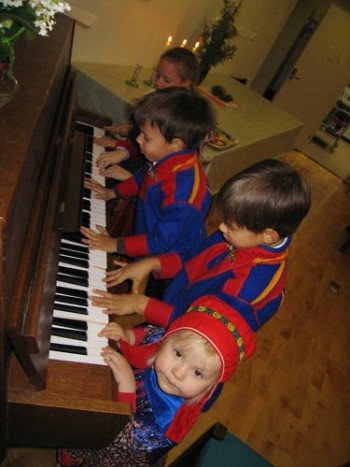 Children try the piano at a City-Sámit Christmas party.
