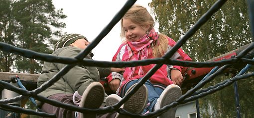 Smiling schoolchildren playing in a jungle gym.