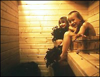 Two smiling children sitting in the sauna.