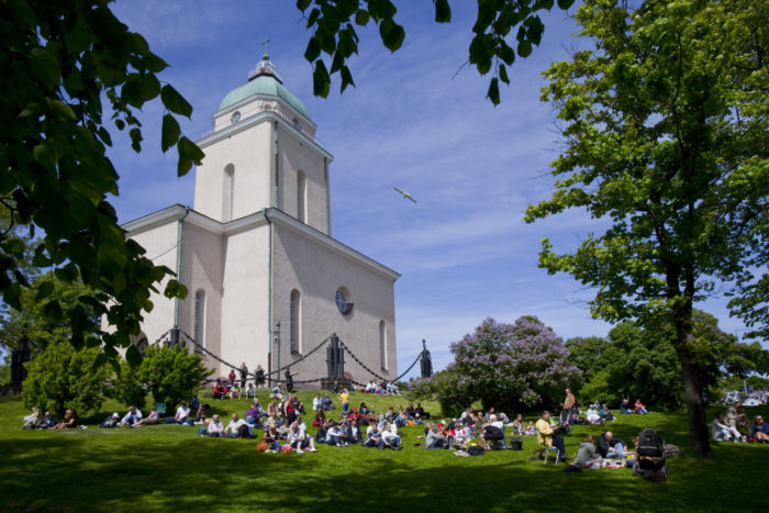 People picnicking on the lawn in front of Helsinki's Suomenlinna Church and its tower.