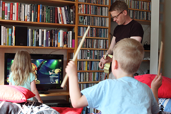 Orgulho de estarem na música pesada: Petri e os filhos agitam na música de metal réptil dentro da sala de estar.