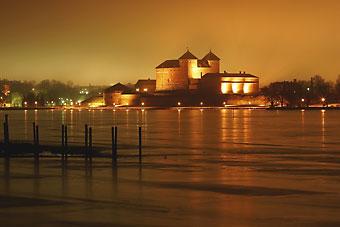 Häme Castle seen in evening light across the lake.