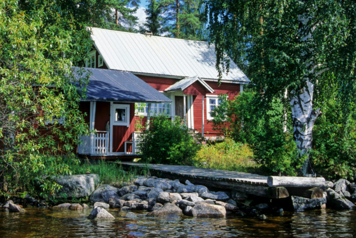 A red summer cottage by a lake with a pier leading up to a sauna building.