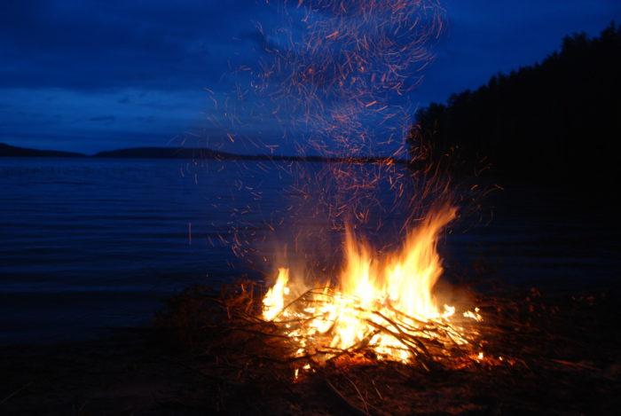 A bonfire against a blue lake view.
