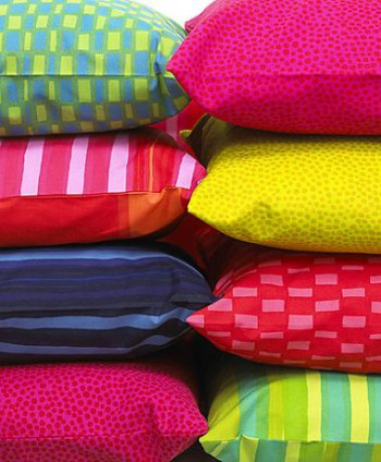 Two piles of colourful pillows.
