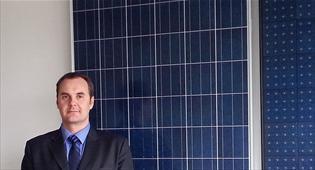 Председатель правления Эса Арева на фоне солнечных панелей.