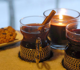 Two glasses of glögi and a cookie sitting by a candle on a snow-covered table.