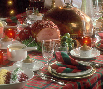 A Christmas table set with red and green tablecloth and napkins; a big ham and other dishes on the table.