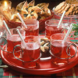 Five glasses of glögg on a red tray; almonds and raisins in the middle.