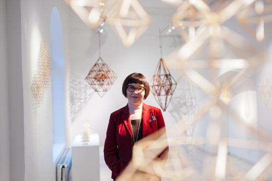 Eija Koski pictured in a white room with multiple himmelis hanging from the ceiling.