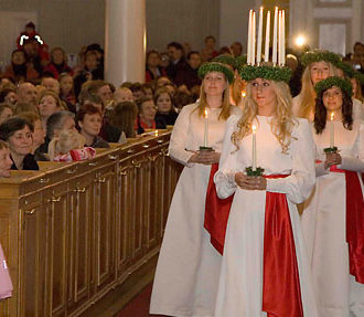 A church filled with people watching the Lucia procession; a group of white-clad girls with wreaths on their heads carrying candles.