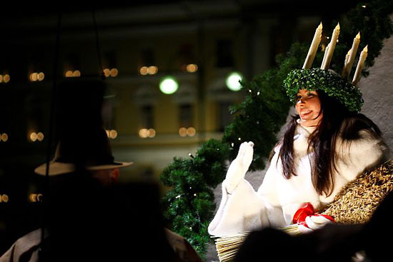 Smiling Lucia with her signature wreath of candles on her head waving from her seat.