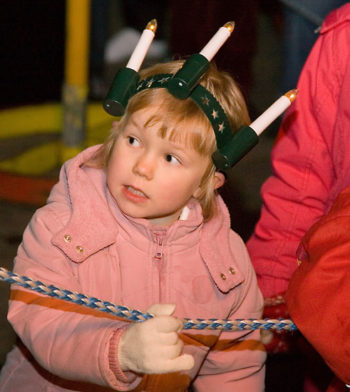 An eager-looking young child dressed in Lucia's wreath of candles.
