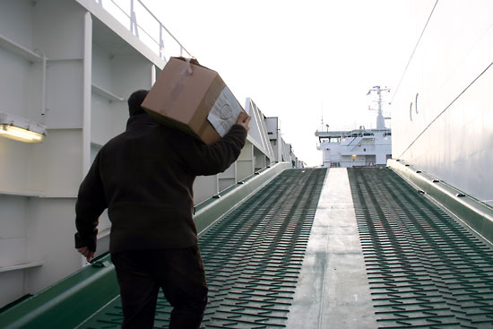 Loads of gifts: Pastor Juha Rintamäki of the Seamen's Mission takes a turn carrying gifts up the gangplank.