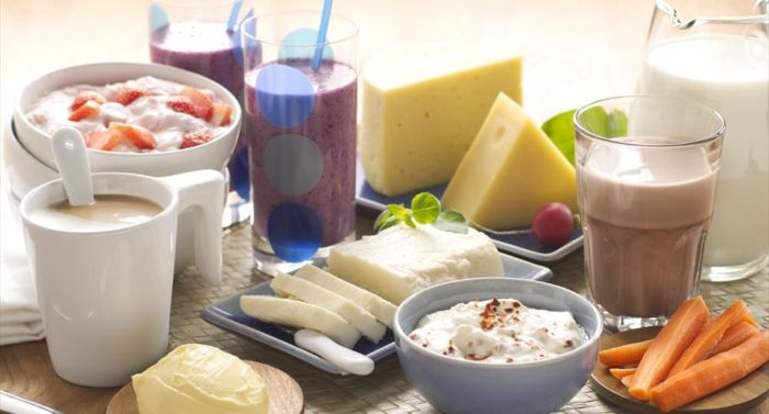 A display of different dairy products: yoghurt, smoothies, milk coffee, cheese and butter.