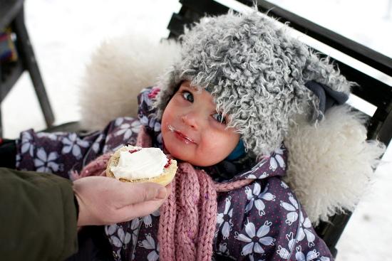 Le restaurant Puutarhatontut (Les Nains de Jardin), Tampere : Anni, 2 ans, se régale d'un gâteau à la crème lors d'un Restaurant Day hivernal. (Photo: Ella Kiviniemi/Restaurant Day)