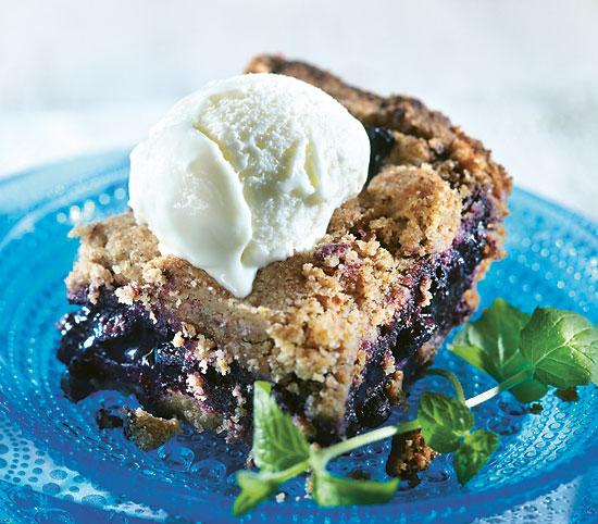 Blueberry pie-like dessert with a scoop of vanilla ice cream.