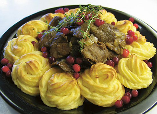 A plate with meat, mashed potatoes and lingonberries.
