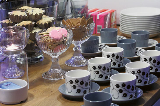 A table set with coffee cups and bowls of cookies.