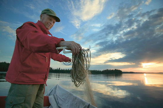 A man standing by a lake untangling a fishing line.