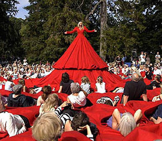 A character in a red dress; people sitting on the huge hem of the dress.