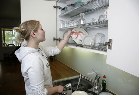 A woman placing dishes to a dish-drying cupboard.