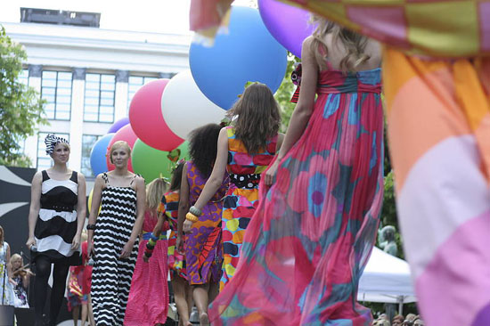 Models on a runway showing Marimekko's dresses and holding big colourful balloons.