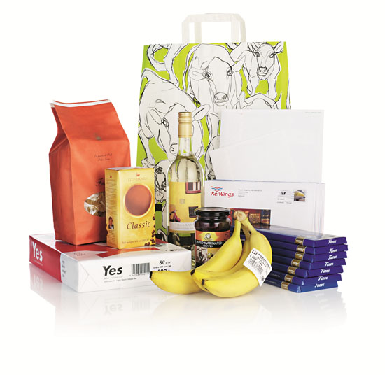 A bunch of different products, such as chocolate bars, a paper bag with images of cows, a wine bottle and bananas.