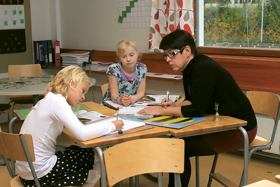 A teacher helping two schoolchildren with their studies.