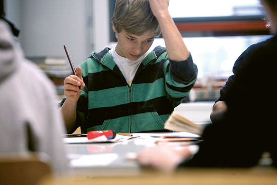 A thoughtful-looking student with pencil in hand looking at papers in front of him.