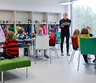 Schoolchildren in a light open space listening to their teacher reading a book.