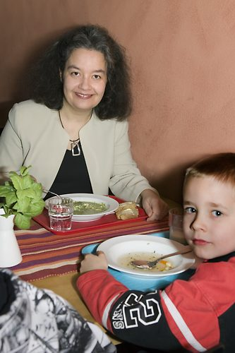 Pupils and teachers eat lunch together in a cosy lunch room.