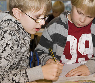 Two schoolboys studying a book.