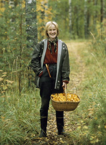 A smiling woman with a basket full of chantarelles.