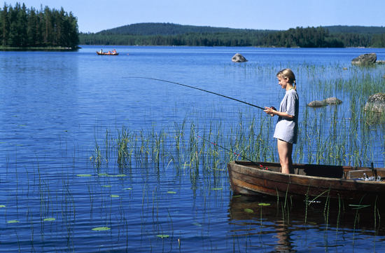 A girl standing in a boat fishing on a clear blue lake.