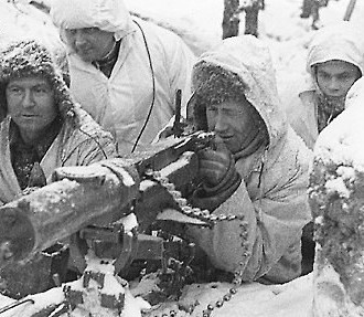 A black and white photo of four Finnish soldiers on guard behind a machine gun.