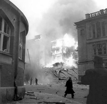 A black and white photo showing a collapsed building on fire and people walking on the street in front of it.