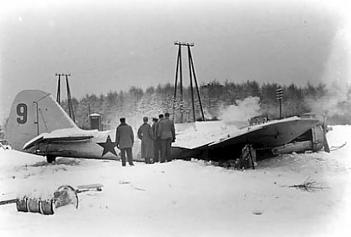 A black and white photo of a group of soldiers inspecting a Soviet bomber.