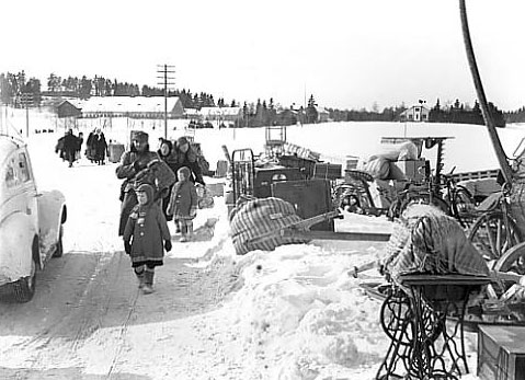 A black and white photo of evacuees from Karelia walking on a snowy road.