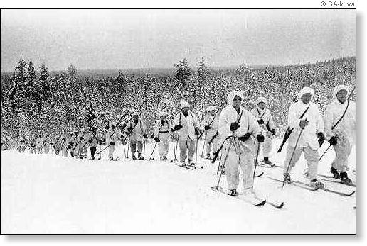 A black-and-white photo of Finnish ski troops in their white gear skiing in a forest.