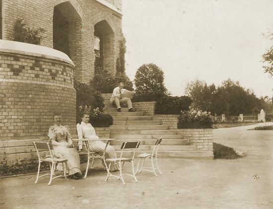 Foto des Herrensitz Uskpenskoje. Links sitzen Mannerheims Frau Anastasia Arapova und Tochter Sophie Mannerheim. Mannerheim selbst sitzt auf den Stufen.