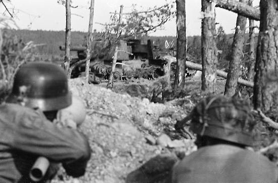 In the background, a Russian KV2 assault vehicle destroyed by Finnish anti-tank fire (foreground) at a crossroads between Ihantala and Karisalmi.