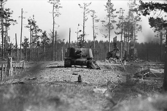A Russian tank in position in front of a burned-out rural post office (background).