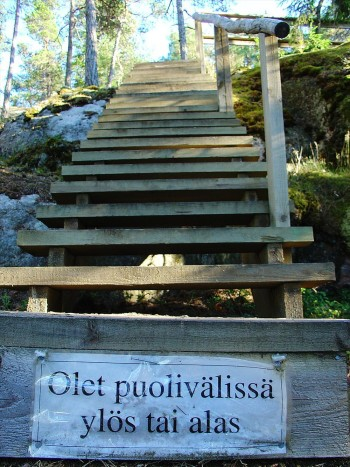 "Wooden stairs in the forest with a sign saying ""You're either halfway up or halfway down."""