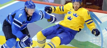 A Finnish and Swedish hockey player battling in the rink.